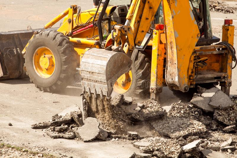 Bulldozer Dismantles Asphalt at Work. Yellow Excavator Dig the Asphalt with Tractor Bucket. Bulldozer Dismantles Asphalt at Work royalty free stock images