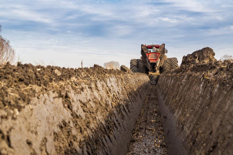 Tractor with double wheeled ditcher digging drainage canal. Agricultural activity royalty free stock images