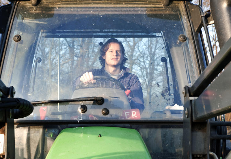 Tractor driver. Farm hand behind the wheel of a tractor, seen through the windscreen royalty free stock photo