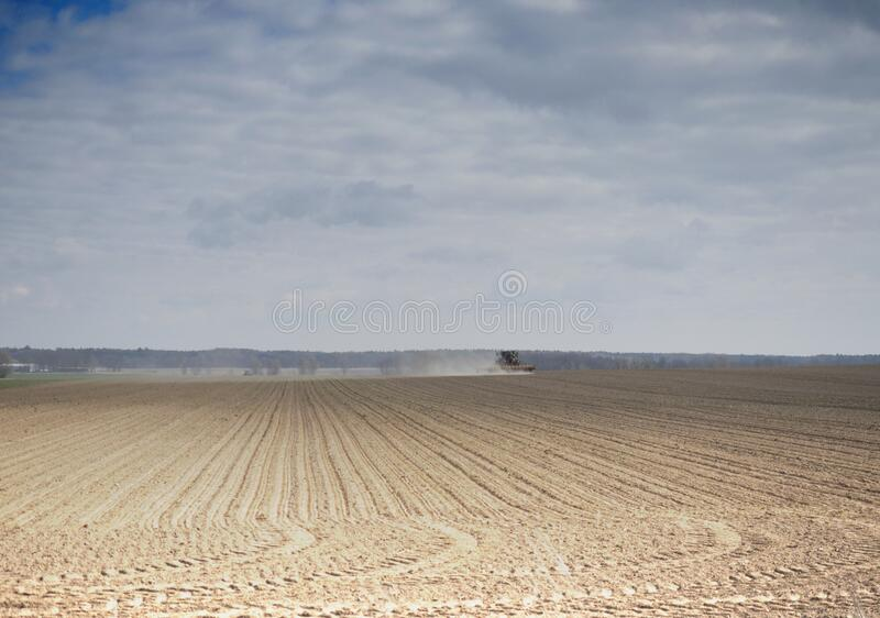 Tractor driving across the field stock photos