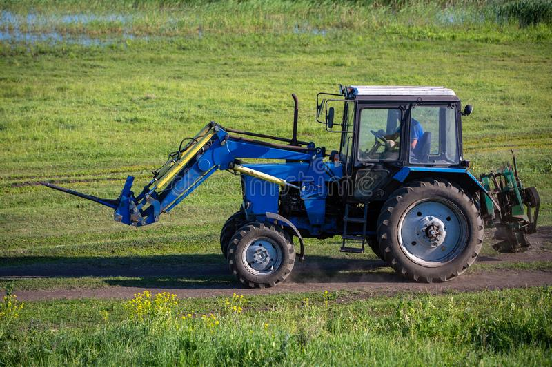 A tractor is driving along a road in a meadow. Summer sunny day. Russian province royalty free stock photos