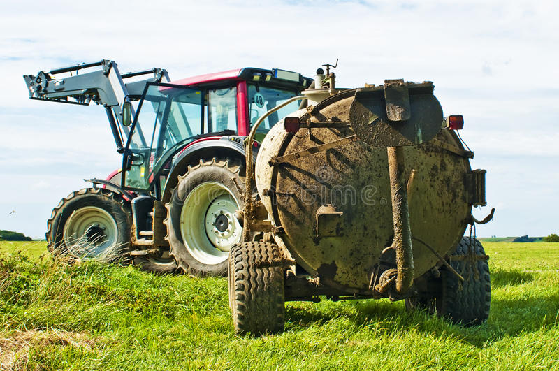 Tractor with dung. Trailer on a meadow royalty free stock image