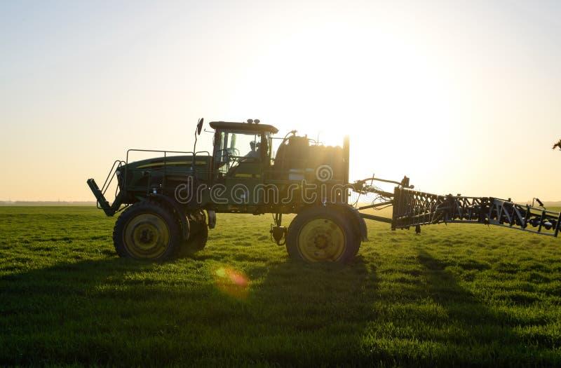 Tractor en el fondo de la puesta del sol El tractor con las altas ruedas est? haciendo el fertilizante en trigo joven El uso del  fotos de archivo