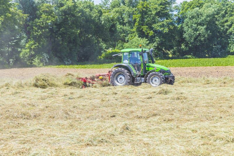 Tractor en el prado que hace el heno imagen de archivo libre de regalías