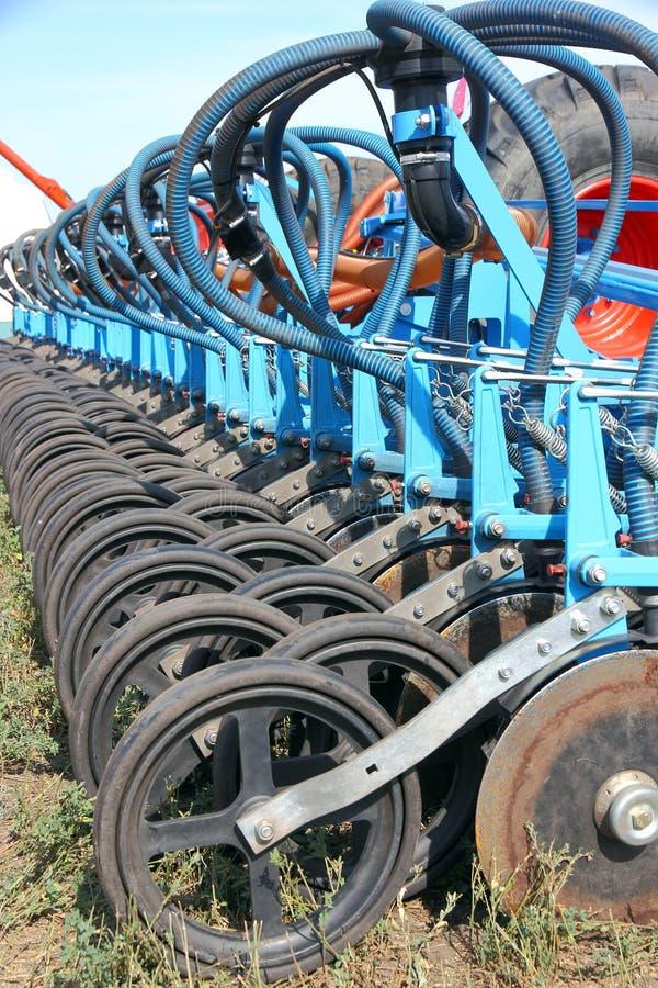 Tractor en zaaimachine die gewassen op een gebied planten stock foto