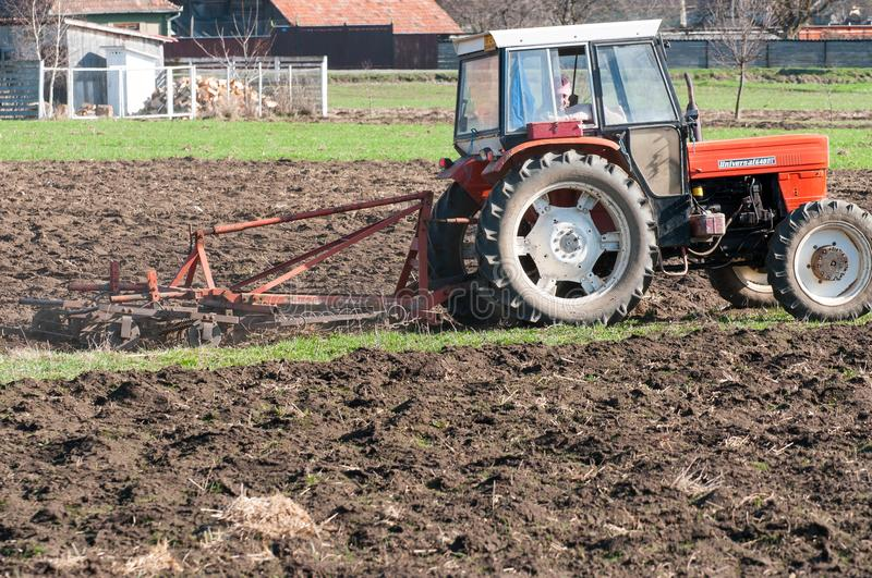 Tractor equipped with harrow working on the field royalty free stock photography