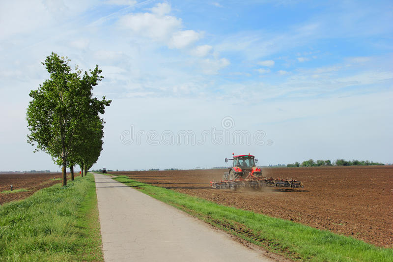 Tractor on a farm field working with a disc harrow stock images