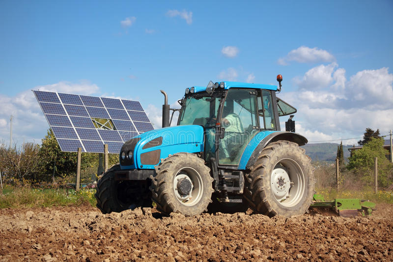 Tractor farming in field and solar panel royalty free stock images