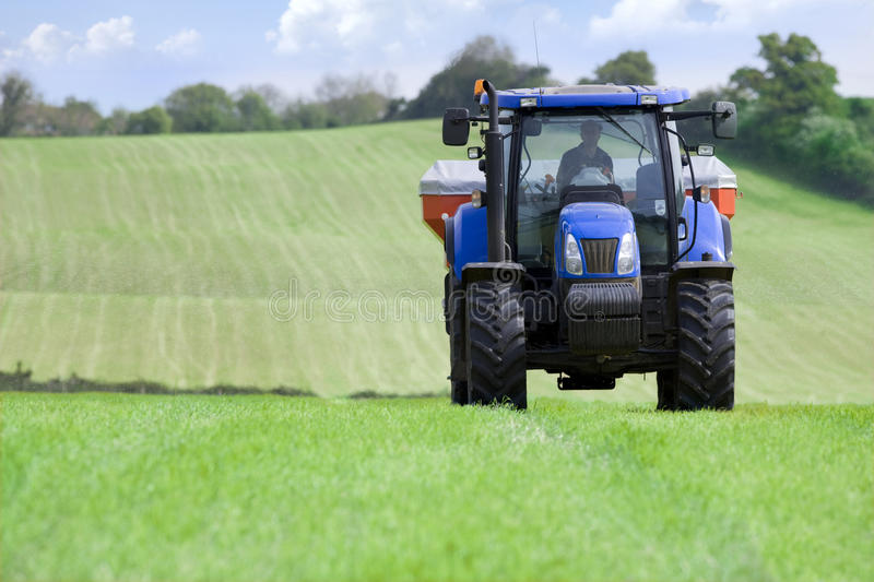 Tractor and fertilizer spreader in field stock photo
