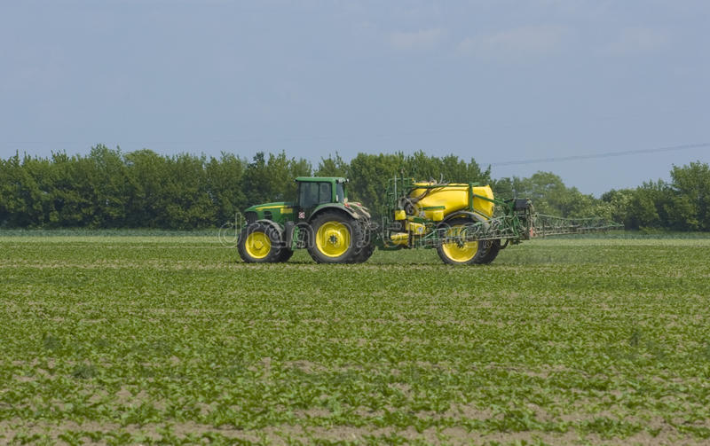 Tractor fertilizing field royalty free stock photography