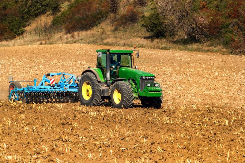 Tractor on the field. Cultivation for loosening the soil. Tractor cultivates field. Autumn work on agricultural farmin in the stock image