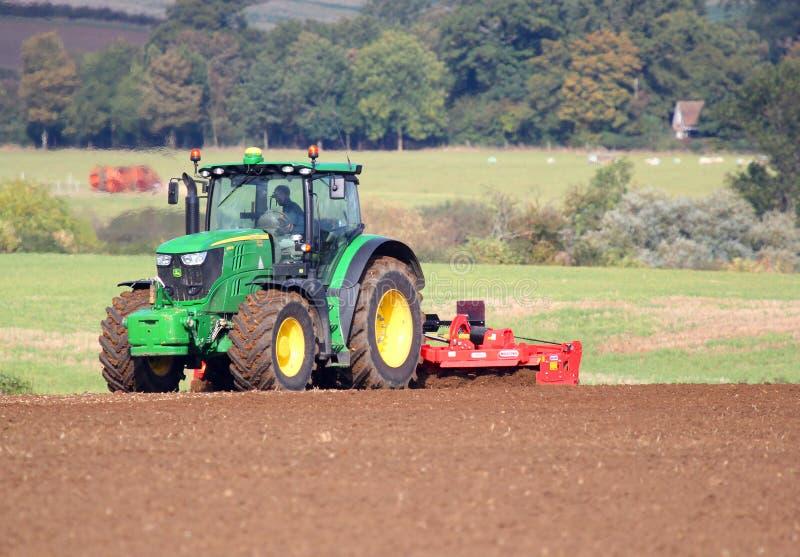 Tractor harrowing field. stock images