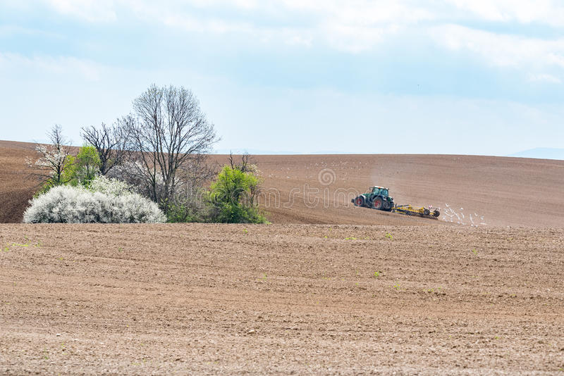 Tractor harrowing the field. Large view on the tractor harrowing the field in spring season stock images