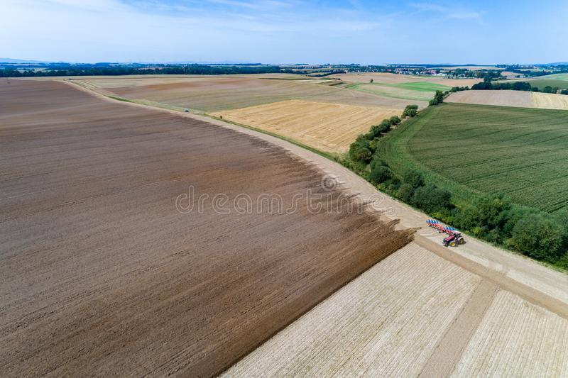 Tractor harrownig the large brown field stock photos