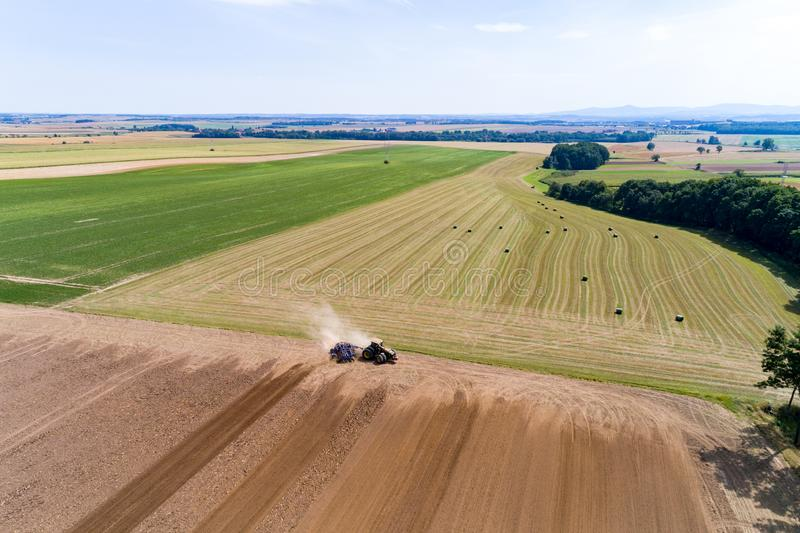Tractor harrownig the large brown field royalty free stock image
