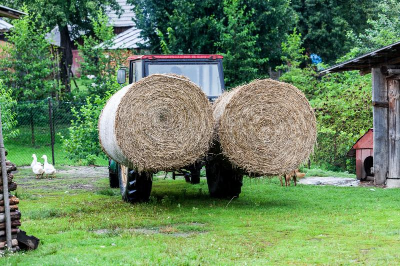 Tractor with large round bales of straw. Village works with tractor. Hay bales production on the village. Village. Scenery with peasent tools in the backyard royalty free stock images