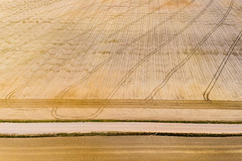 Tractor left long track patterns while ploughing dry farmlands, aerial landscape. Agriculture concept. Tractor left long track patterns while ploughing the dry royalty free stock photo