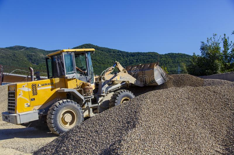 Tractor-loader loads rubble on a bright Sunny day. Piles of rubble. stock images