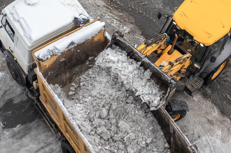 Tractor loader machine uploading dirty snow into dump truck. Cleaning city street, removing snow and ice after heavy. Snowfalls and blizzard stock images