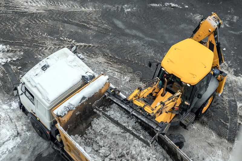 Tractor loader machine uploading dirty snow into dump truck. Cleaning city street, removing snow and ice after heavy. Snowfalls and blizzard royalty free stock photography