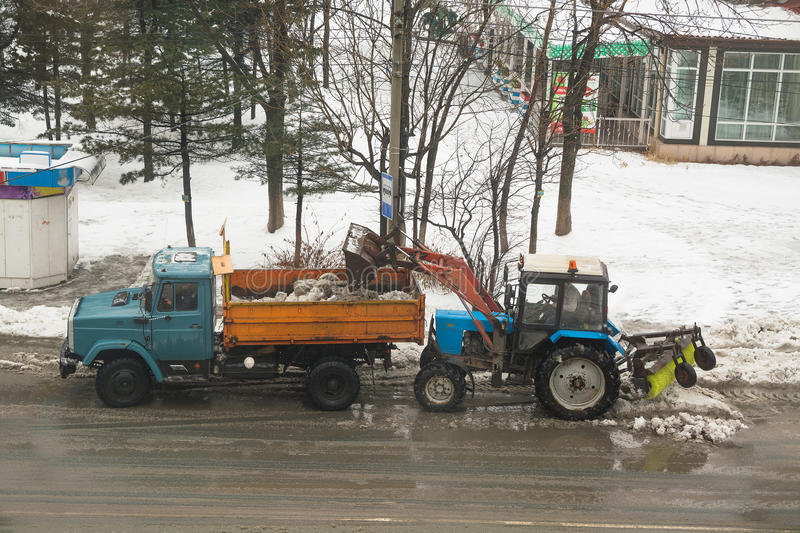 Tractor loads snow on the dump truck. Top view on the roadway royalty free stock image