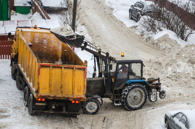 Tractor loads the snow in the truck for snow removal from the city. Snow cleaning tractor snow-removal machine loading pile of snow on a dump truck. Snow plow royalty free stock photos