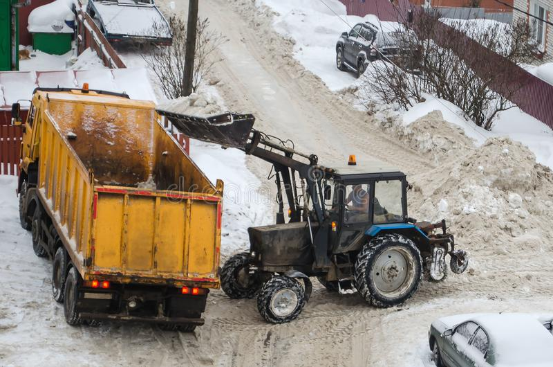 Tractor loads the snow in the truck for snow removal from the city. Snow cleaning tractor snow-removal machine loading pile of snow on a dump truck. Snow plow royalty free stock photo
