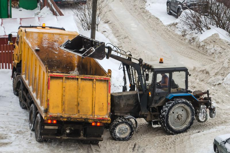 Tractor loads the snow in the truck for snow removal from the city. Snow cleaning tractor snow-removal machine loading pile of snow on a dump truck. Snow plow stock photo