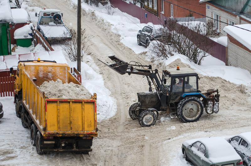 Tractor loads the snow in the truck for snow removal from the city. Snow cleaning tractor snow-removal machine loading pile of snow on a dump truck. Snow plow stock image