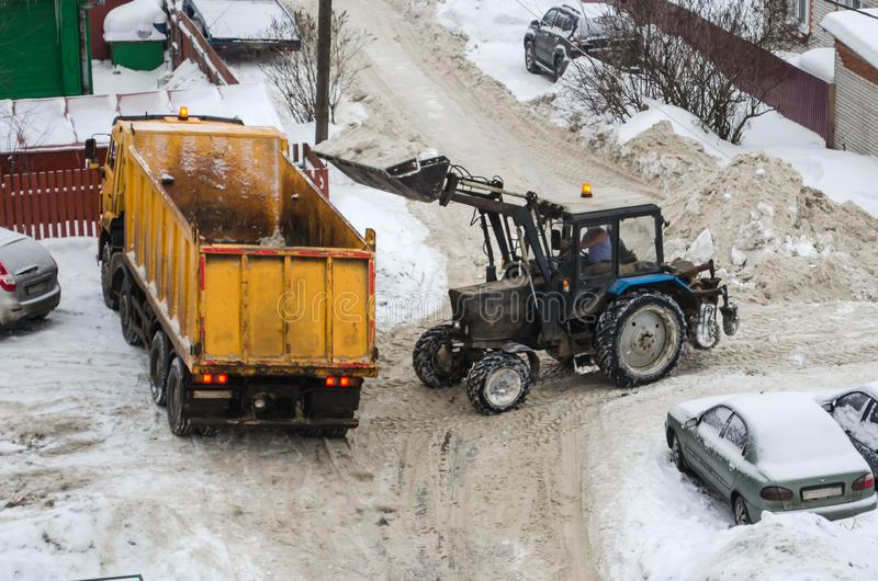 Tractor loads the snow in the truck for snow removal from the city. Snow cleaning tractor snow-removal machine loading pile of snow on a dump truck. Snow plow royalty free stock image