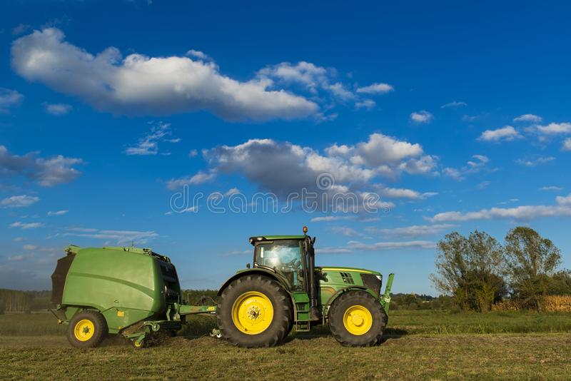 Tractor with machinery for making bales of hay stock photography