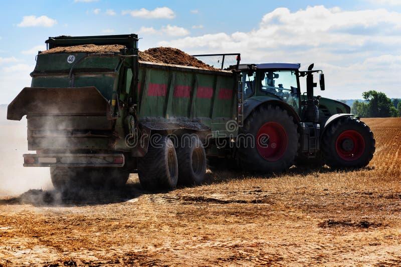 Tractor met aanhangwagenhoogtepunt van organische meststof of mest aan stock afbeelding