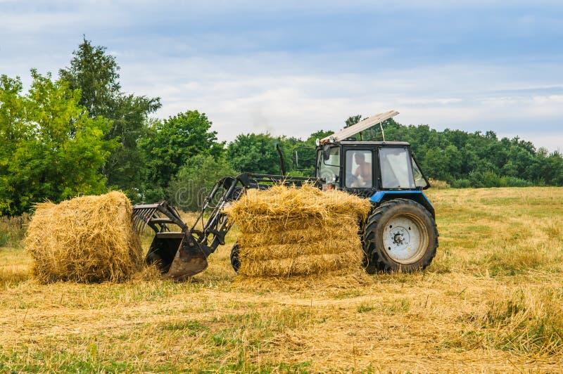 Tractor met een hooi stock afbeelding