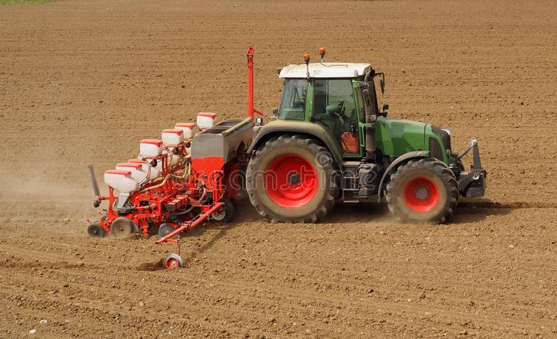 Tractor met een moderne het zaaien zadenmachine op een onlangs geploegd gebied in de lente Zachte nadruk Geploegd land op achterg royalty-vrije stock afbeelding
