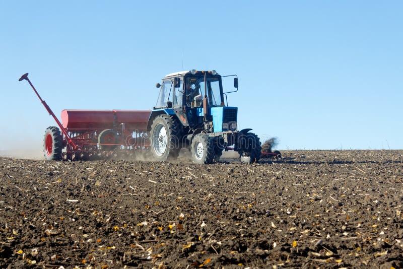 Tractor met een zaaimachine op het gebied stock foto's
