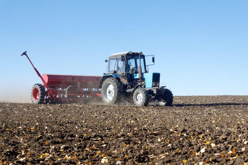 Tractor met een zaaimachine op het gebied stock afbeeldingen