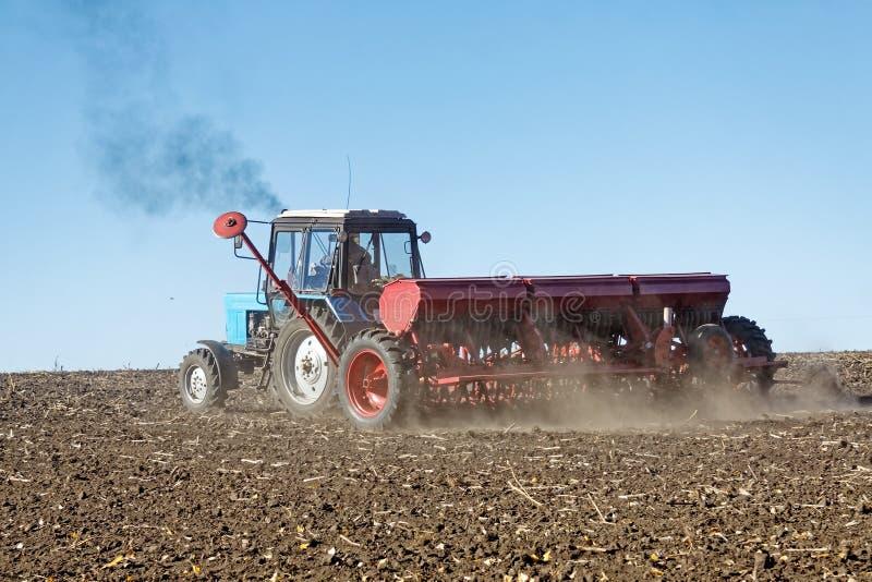 Tractor met een zaaimachine op het gebied royalty-vrije stock afbeeldingen