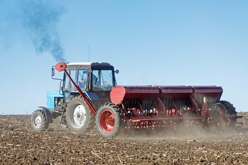 Tractor met een zaaimachine op het gebied stock foto