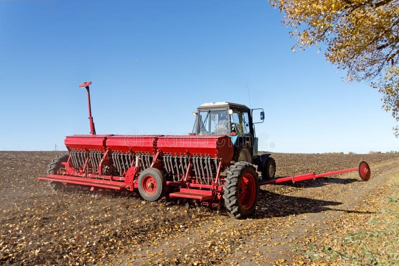 Tractor met een zaaimachine op het gebied stock afbeelding