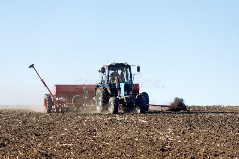 Tractor met een zaaimachine op het gebied stock fotografie
