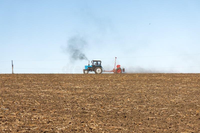 Tractor met een zaaimachine op het gebied royalty-vrije stock afbeelding