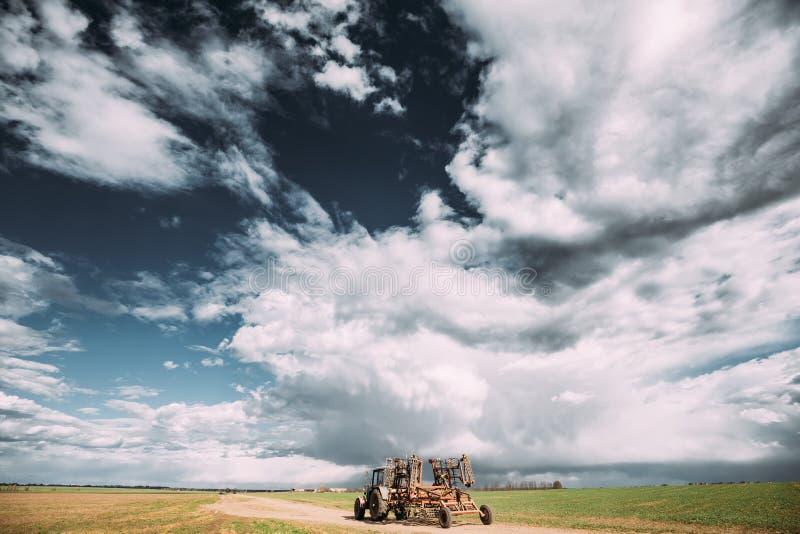 Tractor met Eg In bijlage in Sunny Spring Day Platteland Ru royalty-vrije stock afbeelding