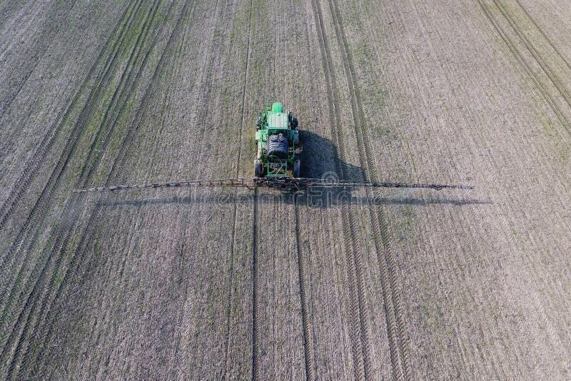 Tractor met scharnierend systeem om pesticiden te bespuiten Bevruchtend met een tractor, in de vorm van een aërosol, op het gebie stock fotografie