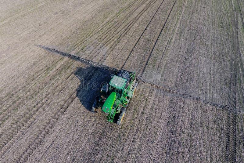 Tractor met scharnierend systeem om pesticiden te bespuiten Bevruchtend met een tractor, in de vorm van een aërosol, op het gebie stock foto