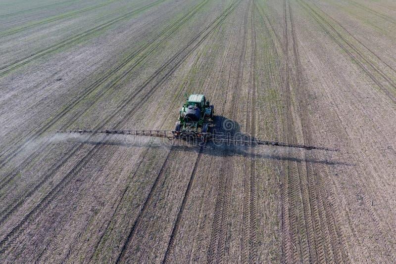 Tractor met scharnierend systeem om pesticiden te bespuiten Bevruchtend met een tractor, in de vorm van een aërosol, op het gebie stock afbeelding