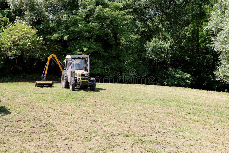 Tractor met strimmer stock afbeelding