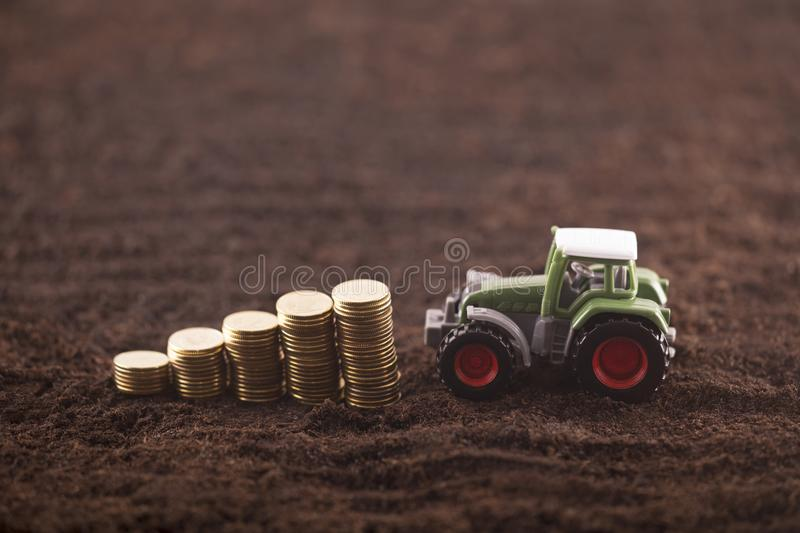 Tractor miniature with coins on fertile soil land stock photography