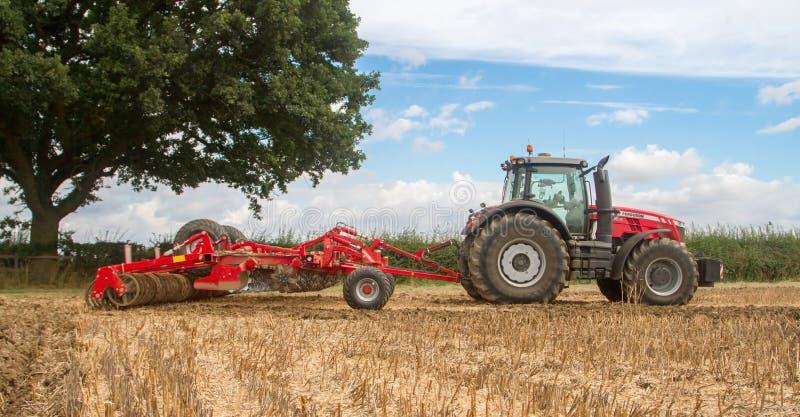 Tractor moderno de ferguson del massey que cultiva el campo imagen de archivo