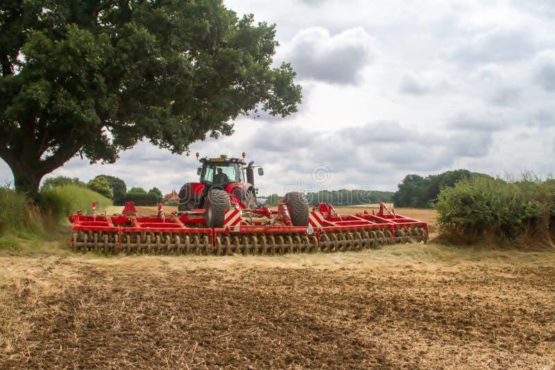 Tractor moderno de ferguson del massey que cultiva el campo fotos de archivo