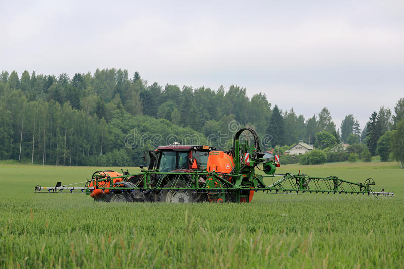 Tractor and Mounted Sprayer on Wheat Field. SALO, FINLAND - JUNE 25, 2016: Farmer sprays wheat field with Valtra tractor and Amazone 1501 UF mounted sprayer in royalty free stock photo
